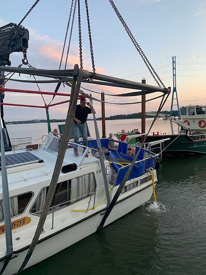 Uponneen veneen nostaminen satamassa.
